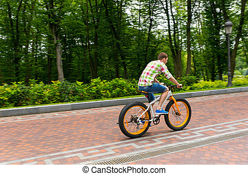 Young man riding a bike on a footpath in a park - Young man...