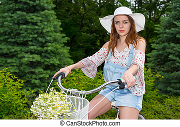 Attractive female wearing a white hat sitting on her bicycle...