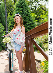 Attractive female standing near her bicycle and smiling -...