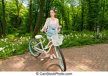 Female with her bicycle standing on bricks in a park -...