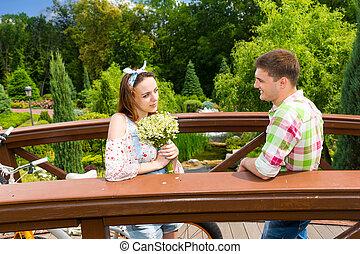 Young couple having a date on a bridge in the park - Young...