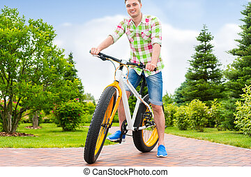 Fabulous handsome man sitting on his bicycle in a park -...