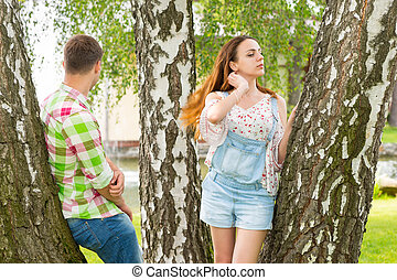Young couple leaning on trees in a park with fountain and...