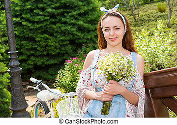 Attractive girl smiling with flowers standing near bike -...