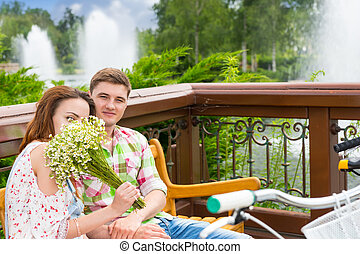 Youg female smelling flowers while sitting on a bench with a...
