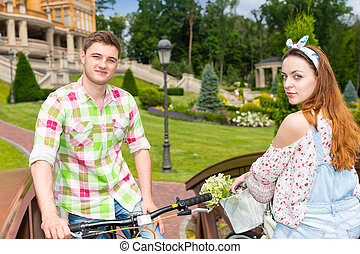Young man and woman stopped riding on bikes on footbridge in...