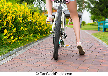 Woman's legs started riding a bike on a footpath in a park