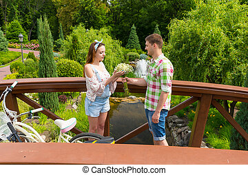 Young romantic man gives flowers to his girlfriend in the...