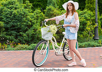 Young woman wearing a white hat standing near her bicycle...
