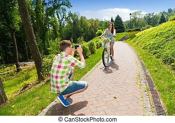 Young guy taking a photo of his girfriend sitting on a bike...