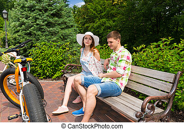 Young couple sitting on bench near bikes in park - Young...