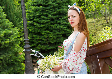 Young girl standing near her bicycle and smiling - Young...