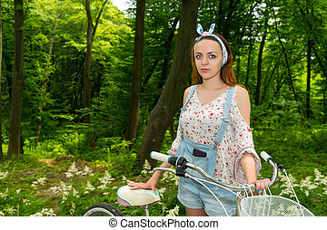 Fasionable female with her bicycle in a park - Fasionable...