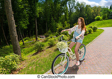 Young woman sitting on her bicycle in a park - Young woman...