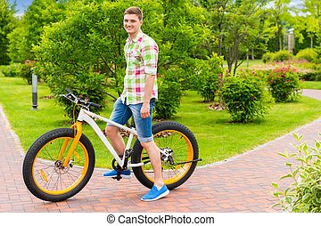 Happy smiling guy sitting on his bicycle in a park - Happy...