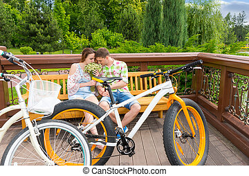 Male and female sitting on a bench and smelling flowers -...