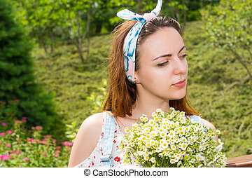 Portrait of a thoughtful young girl holding flowers -...