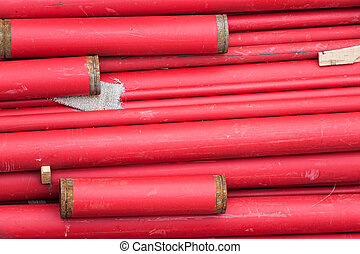 Red metal pipes stacked for working at construction site