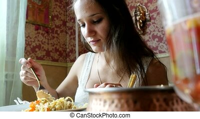 young woman eating spaghetti in cafe. 4k