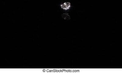 Diamond Drops onto Shiny Black - A single diamond drops onto...