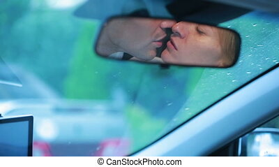 couple kisses, reflected in the car mirror. male and female...