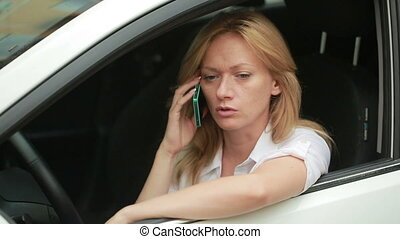 Girl driver talking on the phone while sitting in car. woman in the parking l