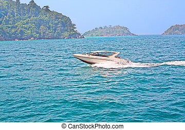Speedboat pass a tropical islands in sunny day