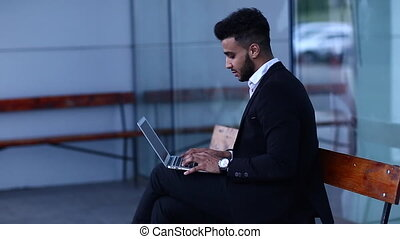 Cool guy arabic man uses laptop in business center