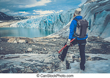 Woman climber standing near Jostedalsbreen glacier. Norway.