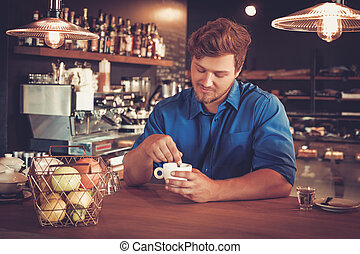 Barista tasting a new type of coffee in his coffee shop. -...