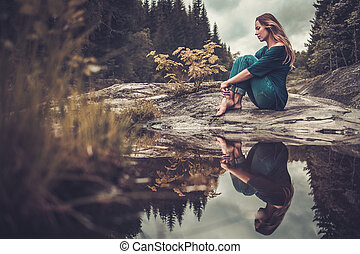 Beautiful woman posing near pond with mountain forest on the...
