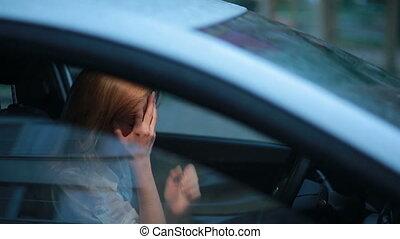sad girl crying in the car. rain on the street. woman in...