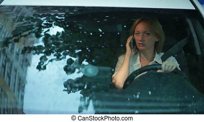 Girl driver talking on the phone while sitting in car. woman in the parking lot