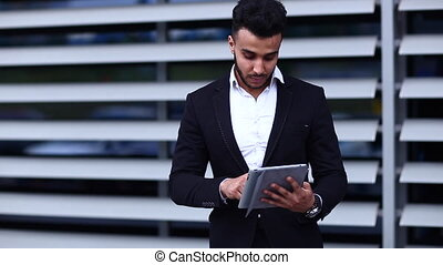Young arabic man uses tablet online order shopping in...
