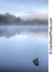 Misty Dawn on a Lake in Ontario, Canada - A distant...
