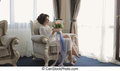 Gentle bride sitting in the chair with the wedding bouquet...