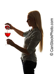 Young woman fills a glass of red wine