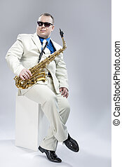 Music Concept. Full Length Portrait of Handsome Caucasian Musician With Alto Saxophone Posing In White Suit Against White Background. Wearing Black Sunglasses