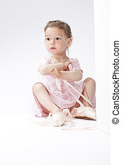 Portrait of Surprised Little Caucasian Ballerina Trying On...