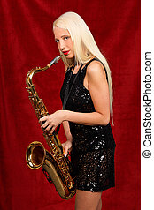 Young pretty woman playing saxophone