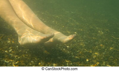Underwater Slow Motion Shot of Female Legs In Sea On Pebbly...