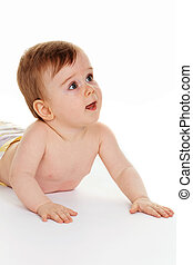Small child in baby diapers is on the ground