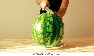 Cutting in half the big fresh and juicy watermelon on a...
