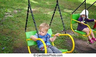 little kids swinging on swings