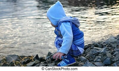 child throwing stones into the river