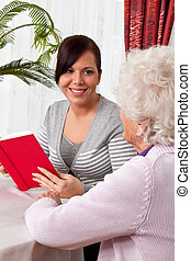Elderly woman reads from a book.