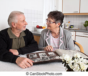 Gl, offenders Elderly couple looking at photo album - Happy...