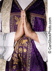 Catholic priests in prayer in worship - a Catholic priest in...