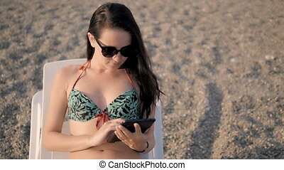 Young Beautiful Woman In Swimming Suit Using Tablet PC On...
