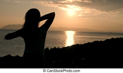 Back Side View On a Silhouette of Wonderful Young Woman Watching To Sea And Raising Her Hands On Sunset